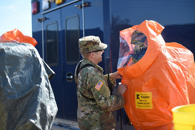 Sgt. 1st Class Daniel Gumm (left), survey team member with the 84th Civil Support Team, assists Pfc. Billy Newman, survey team member with the 84th Civil Support Team, with the final steps of donning his chemical suit.